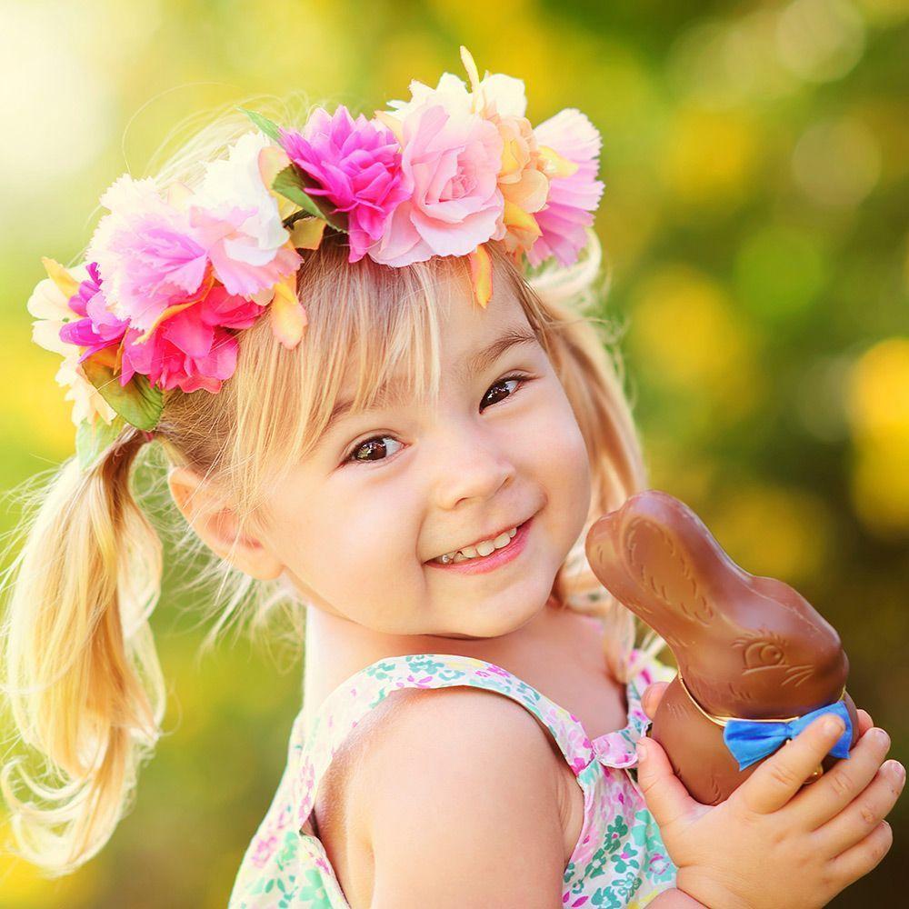 Kleines Mädchen mit Blumenkranz auf dem Kopf mit Schokoladenosterhase