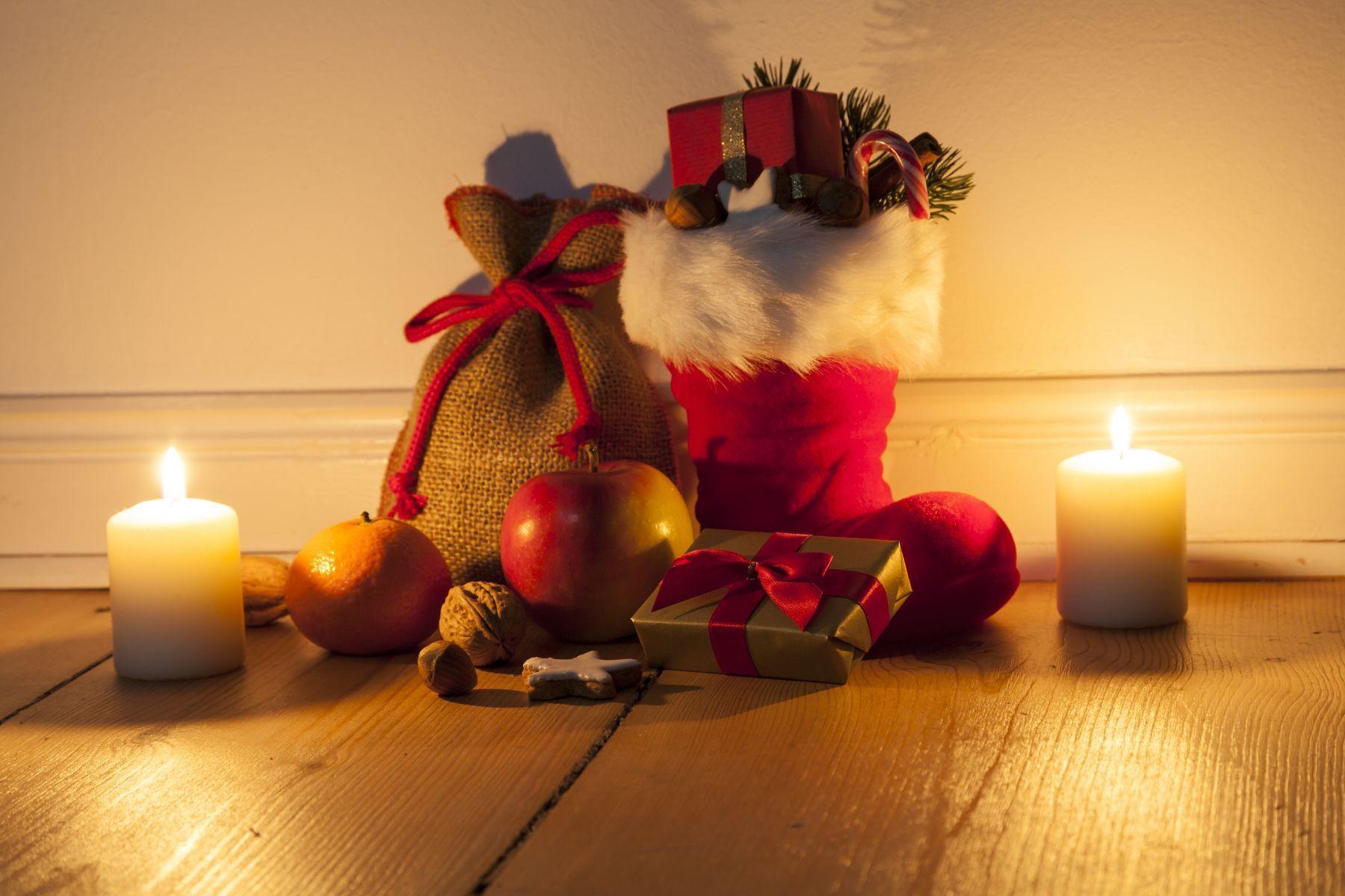 Roter Stiefel mit Geschenken und Äpfeln bei Kerzenlicht