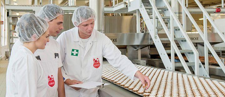 3 Mitarbeiter begutachten die am Laufband hergestellten Lebkuchen
