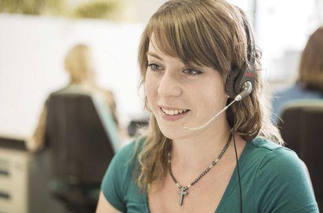 Mitarbeiterin mit Headset am Ohr