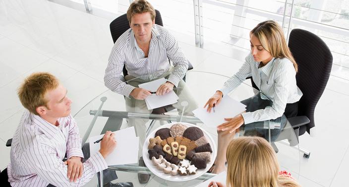 4 Personen beim Meeting mit Lebkuchen auf dem Tisch