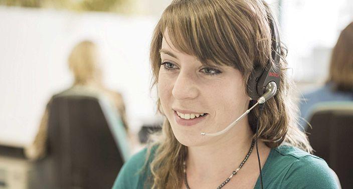 Call-Center-Mitarbeiterin mit Headset am Ohr